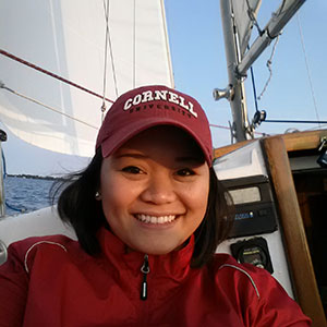 Gage Javier on a sailboat with a sail and mast and blue sky in the bacground